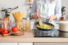 Woman Cooking Tasty Rice With Vegetables On Stove In Kitchen, Closeup