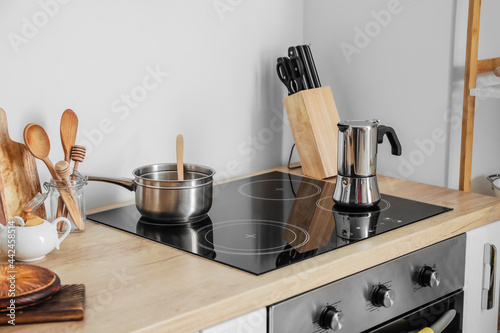 Modern electric stove with cooking pot and coffee maker in kitchen Fotobehang