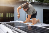 Fototapeta Miasto - Mounting of solar panels on top of a camper van