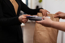 Close Up Of Business Woman Holding Credit Card Of Pos, Using Contactless Technology, Pay For Takeaway Food From Courier. Holding Box With Meal Lunch In Paper Bag.