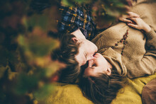 Top View Couple In Love, Lying On Fallen Leaves In Autumn City Park Outdoors. Love Relationship Family Lifestyle.