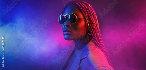 Fotografie, Obraz colorful neon filtered shot of a beautiful young afro woman posing in the studio