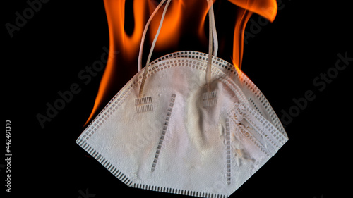 Obraz na plátně Burning Medical Mask on Black Background