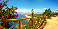Panorama Resort Antalya With Soft Focusing In Background. Sea, Wide Beach, Blue Sky, White Clouds And Chain Of Mountains. Scarlet Oleander Bush, Wood Fence And Retro-style Lanterns Add Charm To Place.