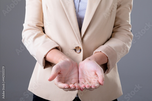 Midsection of caucasian businesswoman showing her hands, isolated on grey background