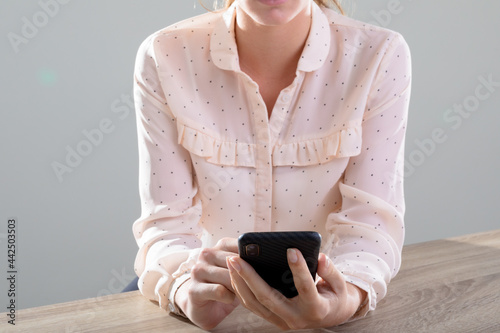 Midsection of caucasian businesswoman using smartphone, isolated on grey background