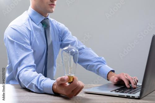 Caucasian businessman holding light bulb using laptop, isolated on grey background