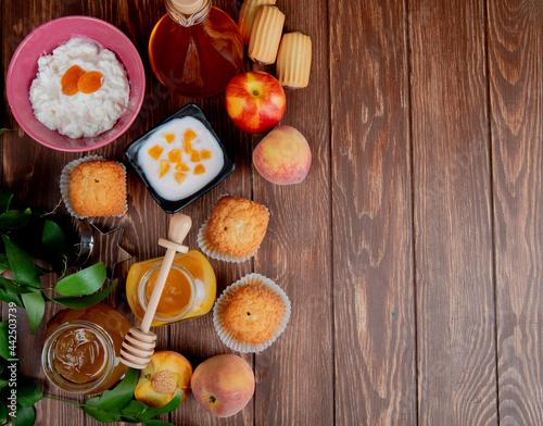 Murais de parede top view of peach yogurt in a black bowl and fresh ripe peaches with muffins coo