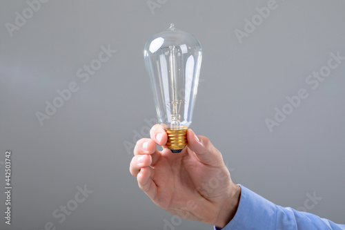 Midsection of caucasian businessman holding light bulb, isolated on grey background