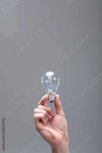 Close up of caucasian businessman holding light bulb, isolated on grey background