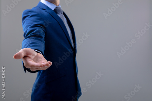 Midsection of caucasian businessman reaching his hand, isolated on grey background