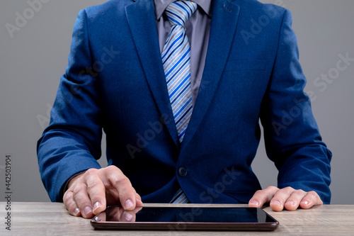Midsection of caucasian businessman using tablet, isolated on grey background