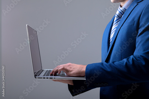 Midsection of caucasian businessman using laptop, isolated on grey background