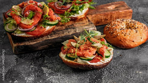 Fotografering Food banner sandwich salad New York bagel with cream cheese, lettuce, cucumber, capers, onions and salted red fish