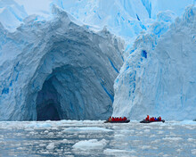 Two Zodiac Vessels Explore The Entrance Of A Large Ice Cave At The Edge Of An Enormous Glacier - Antarctica
