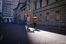 Two Mixed Race Male Friends Carrying Hand Painted Protest Signs Walking In City Street
