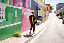Rear View Of Mixed Race Man Carrying Backpack Walking In Colourfully Painted, Sunny City Street
