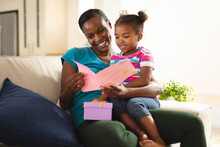 Happy African American Mother And Daughter Sitting On Couch With Card And Present From Daughter