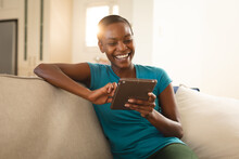 Laughing African American Woman Relaxing, Sitting On Couch Using Tablet