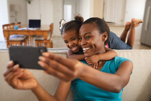 Smiling African American Mother And Daughter Relaxing On Couch And Taking Selfie