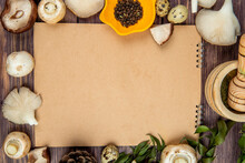 Top View Of Fresh Mushrooms Black Peppercorns Arranged Around A Sketchbook On Rustic Wooden Background