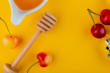 Top View Of Honey With Wooden Spoon And Fresh Ripe Rainier Cherries On Yellow Background