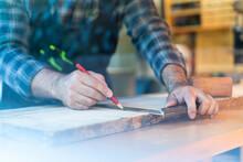 Joiner Measuring Wooden Plank In Workshop