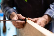 Carpenter Using Marking Gauge For Woodwork