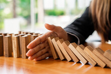A Businesswoman Blocks A Falling Wooden Block Like A Domino. It Is Like Stopping Business Risks With A Strategy. And Project Management The Best Of The Business