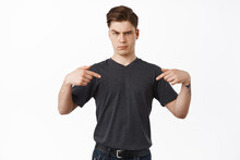 Portrait Of Young Man Looks Doubtful, Pointing Fingers At Logo Showing Something Unusual Strange, Being Unsure Or Skeptical About Product, White Background