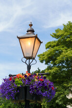 Nostalgic Victorian Lamp Post With Assorted Summer Flowers Hanging In A Basket In A Public Park, Crescent Gardens, Harrogate, North Yorkshire, England, UK.