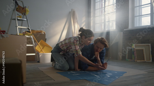 Fotografie, Obraz Focused woman and young man speaking about home repair scheme on floor