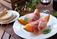 Antipasto Italiano. Fette Di Melone Con Prosciutto Crudo E Pane Toscano. Piatto Estivo.