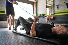 Personal Trainer Holding Resistance Bands. Elderly Man Does Bicep Curl Lying On Mat