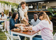 Multiracial People Having Fun Eating At Food Truck Outdoor - Focus On Left Girl Face