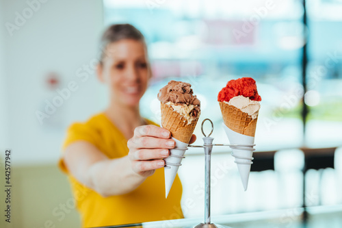 Obraz na plátně Young and happy saleswoman in black apron selling handmade ice cream at the counter of the pastry shop