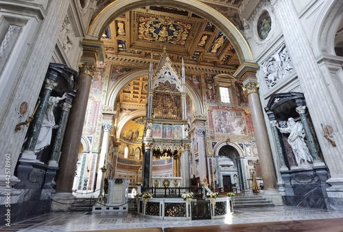 Fototapeta Perspective view of the apse of the Rome cathedral of San Giovanni in Laterano, with the papal altar, the inlaid ceiling and the vault with frescoes