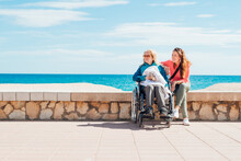 Daughter Sitting With Aged Mother In Wheelchair On Embankment
