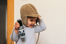 Adorable Baby With A Hat Playing With A Mobile