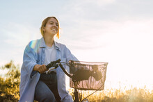 Young Blonde Woman Cycling In A Field At Sunset