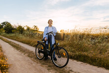 Blonde Woman Standing With A Bike In A Field At Sunset