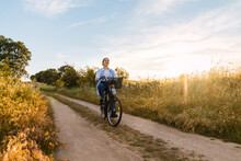 Beauty Young Blonde Woman Cycling In A Field At Sunset