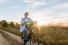 Blonde Woman On A Bike During Sunset In A Field
