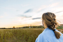 Young Blonde Woman On A Field Looking Sunset