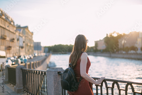 Portrait of a beautiful young woman on the embankment of the river at sunset in summer Fototapeta