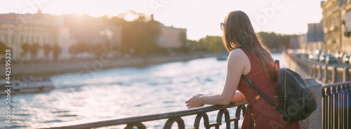 Vászonkép Portrait of a beautiful young woman on the embankment of the river at sunset in summer