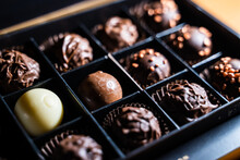 Several Variety Of Chocolate Truffles With Chocolaty And Milky Glaze And Golden Sprinkles With Nuts. Cutting Round Truffle Ball In A Square Box.