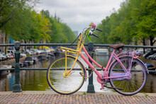 Selective Focus Of Classic Bicycle Parked On Canal Bridge With Blurred Architecture Features Traditional Houses As Background, Amsterdam, Netherlands, Cycling Is A Common Mode Of Transport In Holland.
