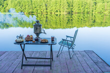 Vintage Metal Tea Samovar With White Smoke And Food On The Table Near The Calm Water Lake In Green Forest At Morning