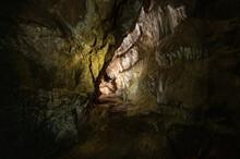 Dark Cave With Stalactites And Stalagmites